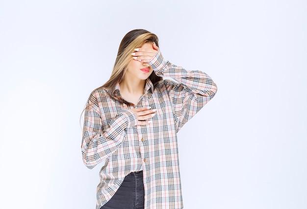 체크 셔츠를 입은 소녀는 창백하고 졸려 보입니다.