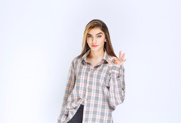 大丈夫な手のサインを示すチェックシャツの女の子