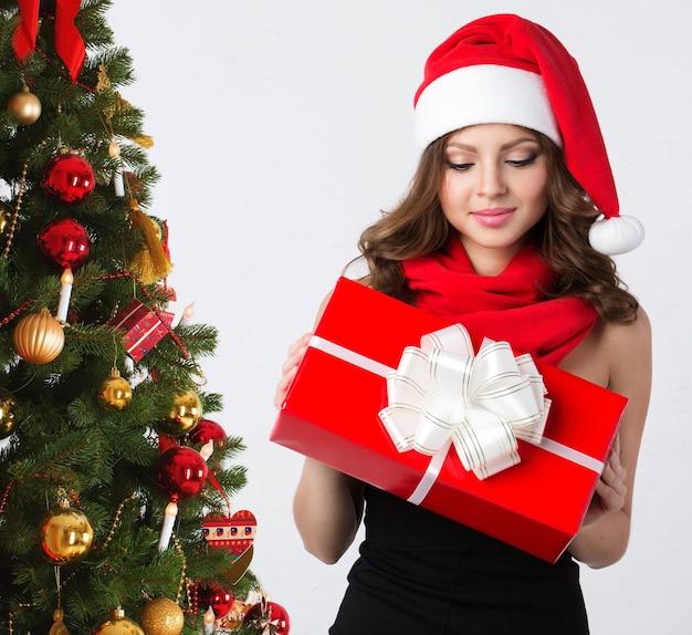 Девушка в рождество. красивая улыбающаяся женщина с подарками