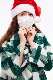 Девушка в рождественской одежде, медицинская маска, рождество, но веселый новый год. фото высокого качества