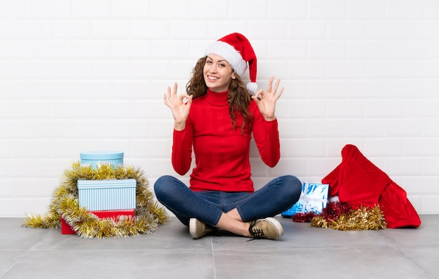 指でokサインを示す床に座ってクリスマス休暇の女の子