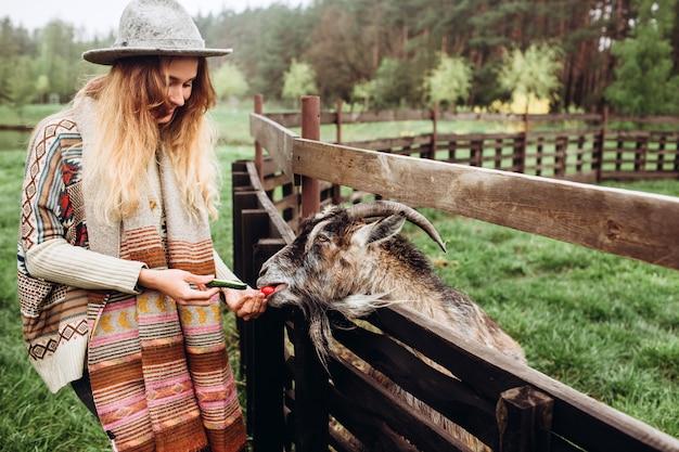 に対してポーズをとって民族パターンの服の女の子、フェンスオン古い農場、農村生活。