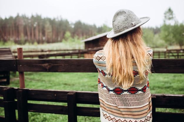 古い農場、農村生活のフェンスを背景にポーズをとって民族パターンの服の女の子。