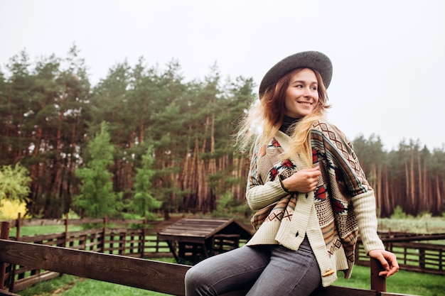 Девушка в одеждах с этническими узорами позирует на фоне забора на старой ферме, сельской жизни.