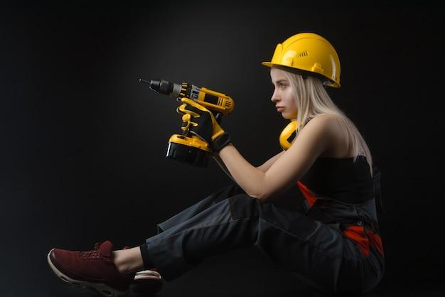 Девушка в строительной одежде и защитном снаряжении позирует с электрической отверткой
