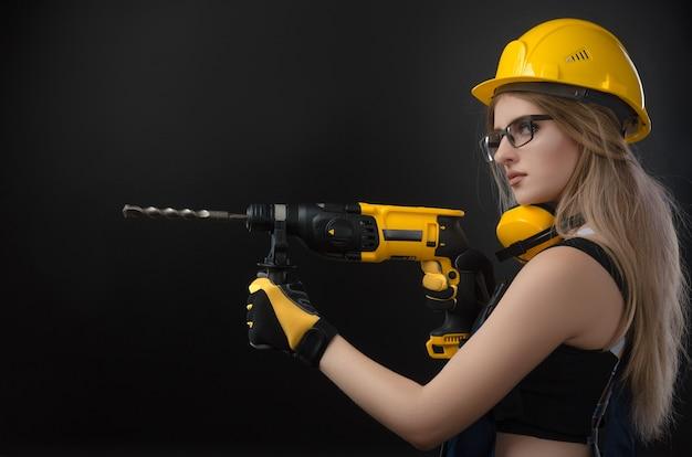 Девушка в строительной одежде и защитном снаряжении позирует с молотком