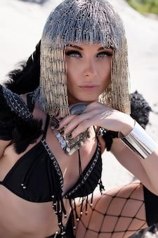 Девушка в творческом фестивальном наряде позирует в пустыне