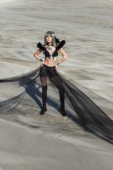 砂漠でポーズをとって創造的な祭りの衣装の女の子