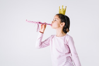 Girl in crown blowing party horn
