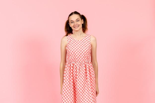ピンクの笑顔の表情でかわいい明るいドレスの女の子