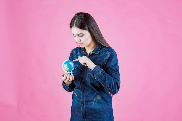 지구상의 장소를 추측하는 데님 재킷을 입은 소녀