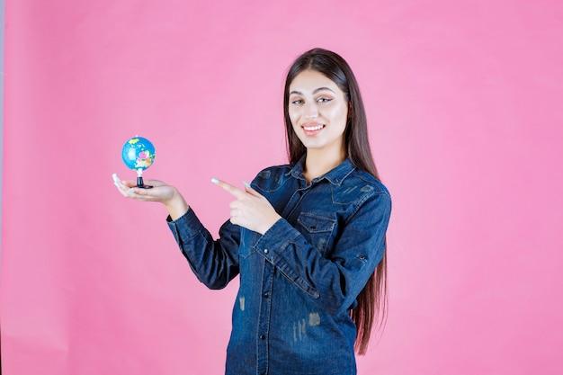 지구본을 가리키는 데님 재킷을 입은 소녀