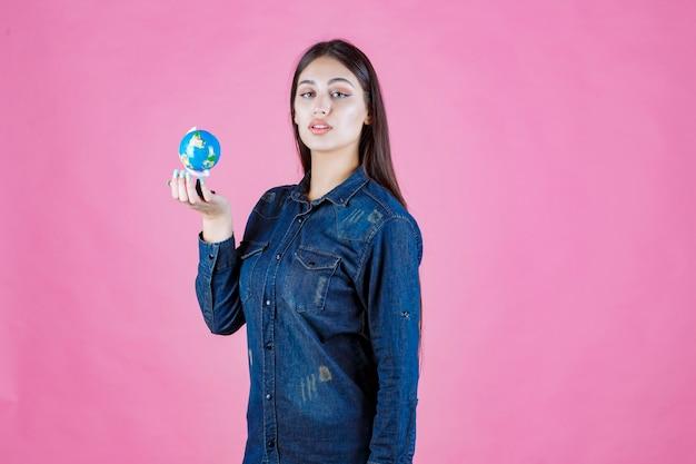 Девушка в джинсовой куртке держит в ладони мини-глобус