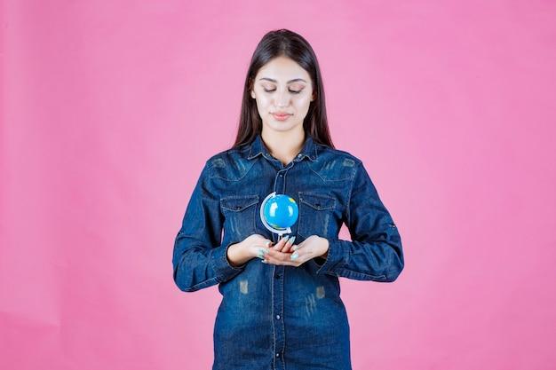 彼女の手のひらの中にミニ地球儀を保持しているデニムジャケットの女の子