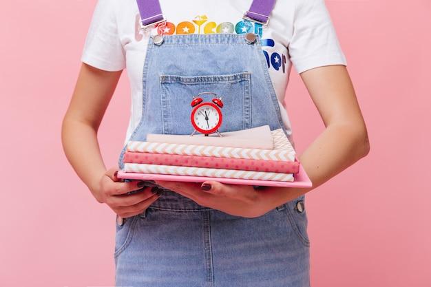 デニムのオーバーオールの女の子はピンクのノートと目覚まし時計を持っています
