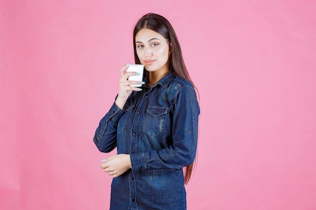 한 잔의 커피를 마시는 데님 셔츠 소녀