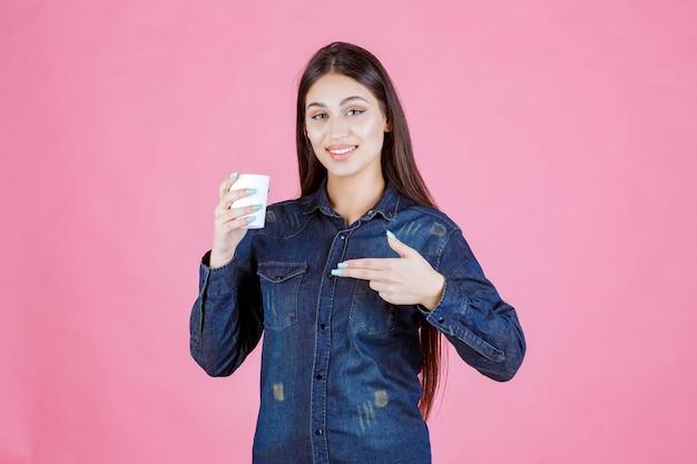 使い捨てのコーヒーを楽しんでいるデニムシャツの女の子
