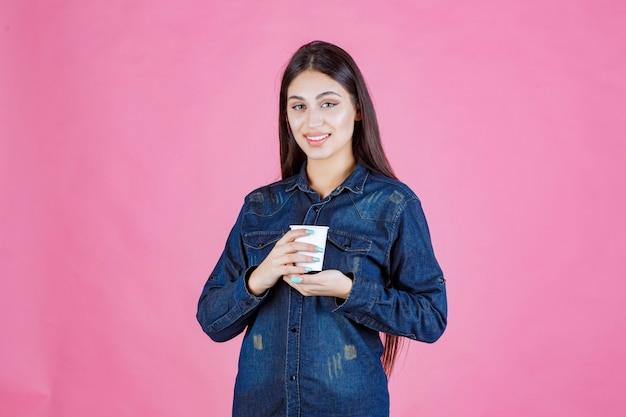 일회용 커피 한 잔을 즐기는 데님 셔츠 소녀