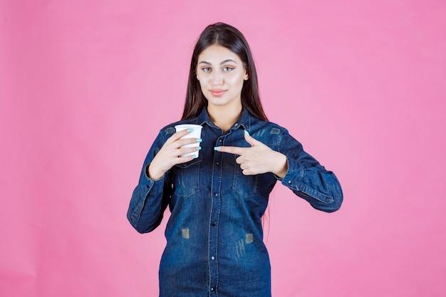 コーヒーカップを持ってポジティブな感じのデニムシャツの女の子