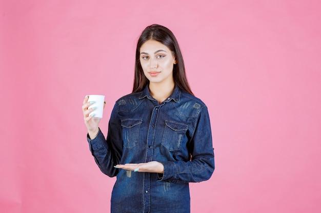 Девушка в джинсовой рубашке держит чашку кофе и чувствует себя уверенно