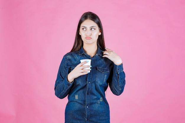 コーヒーカップを持って、思慮深く疑わしいデニムシャツの女の子