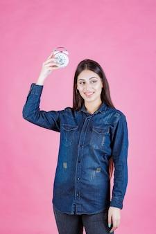 Девушка в джинсовой рубашке держит и продвигает будильник