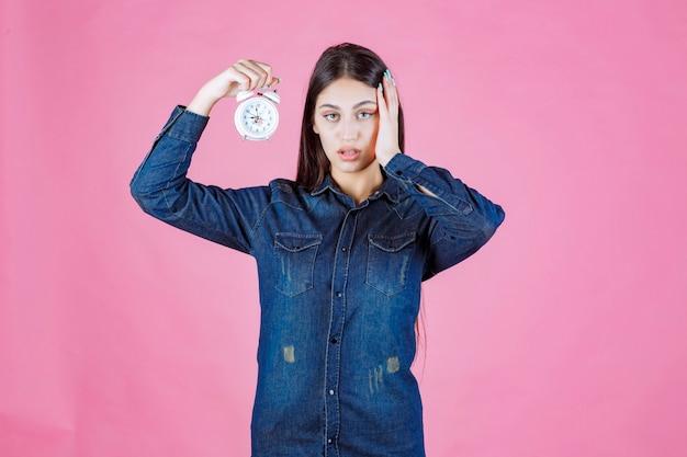 目覚まし時計を持って、リングのために彼女の耳を覆っているデニムシャツの女の子