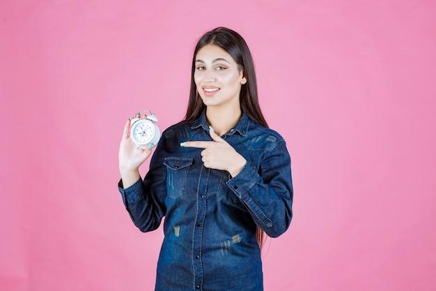 Девушка в джинсовой рубашке держит будильник и указывает на него