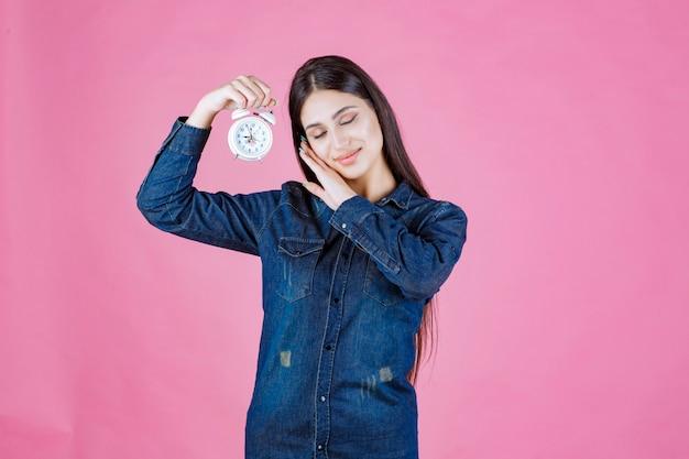 目覚まし時計を持って寝ているデニムシャツの女の子