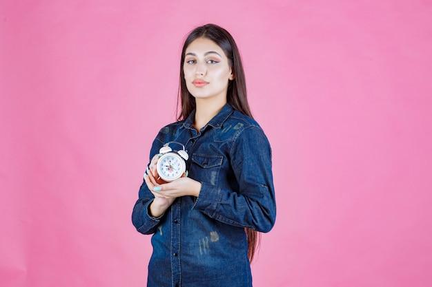 Девушка в джинсовой рубашке держит будильник в руках