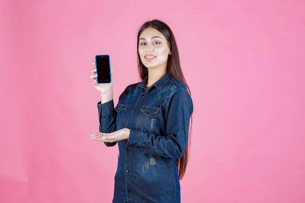 Девушка в джинсовой рубашке показывает свой смартфон и поднимает палец вверх