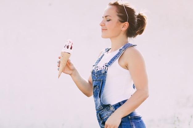 Девушка в джинсовом костюме на светлом фоне ест крем ce