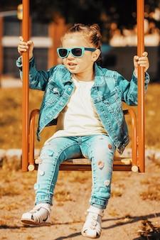 Девушка в джинсовом костюме с темными очками качается на качелях. фото высокого качества