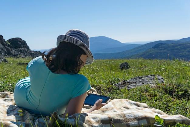 고산 초원에 태블릿과 담요에 앉아 드레스와 모자 소녀