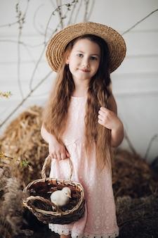 小さなひよこが付いているバスケットを維持するドレスと干し草の帽子の少女