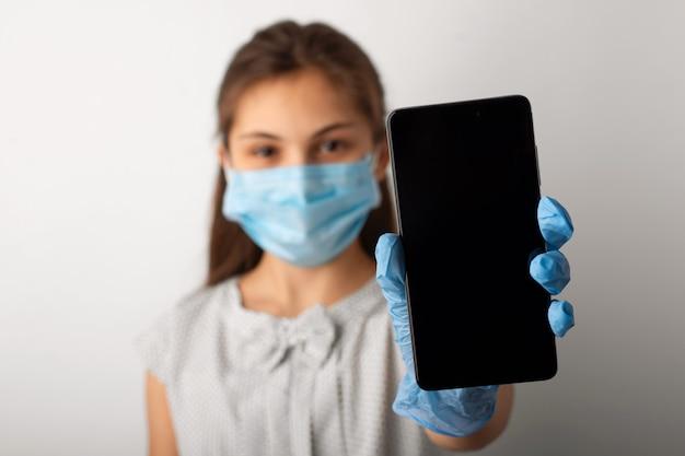 Девушка в платье и защитной маске показывает экран мобильного телефона