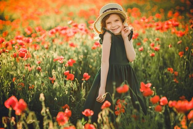 Девушка в платье и соломенной шляпе на открытом воздухе на маковом поле на закате