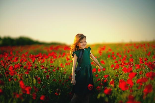 ポピーフィールドで屋外のドレスと麦わら帽子の女の子