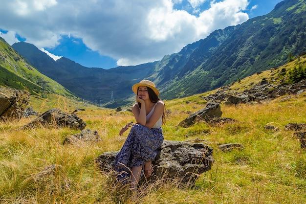 드레스와 밀짚 모자 소녀는 높은 산의 배경에 대해 바위에 앉아있다.