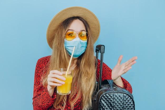 ドレス、帽子、サングラス、彼女の顔に医療用マスクと彼女の手でカクテルの女の子。