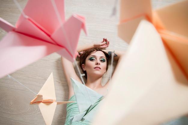Девушка в платье, глядя на бумагу птиц. журавлики оригами.