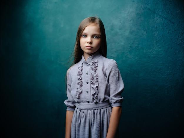 스튜디오 감정을 포즈를 취하는 드레스를 입은 소녀