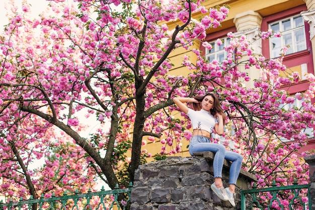 枝の花でポーズをとってドレスの女の子