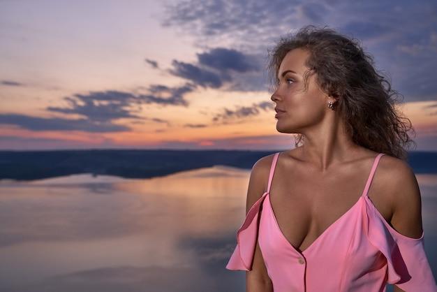 裸の肩と湖の近くのデコルテのドレスを着た女の子