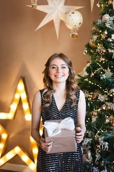 イブニング暗いドレスとクリスマスツリーの女の子