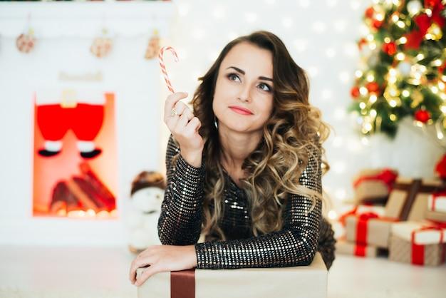 クリスマスツリーと暖炉の前でキャンディケインとイブニングドレスの女の子