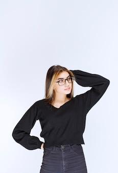 Девушка в очках выглядит задумчивой и нерешительной.