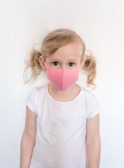 フェイスマスクの女の子。コロナウイルスやインフルエンザの流行時に保護するために、子供はフェイスマスクを着用します。
