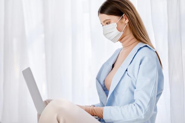 Девушка в защитной маске лица с помощью ноутбука, сидя на полу у себя дома.