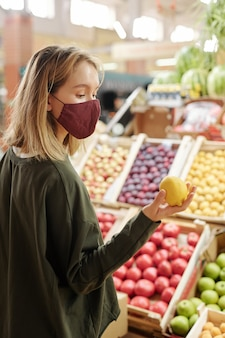 フルーツカウンターに立って、市場でそれを選択しながらレモンを見ている顔のマスクの女の子